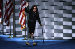 Sen. Lamma Tammy Duckworth, a half-Asian-American woman, walks onto a stage waving with one hand, holding a cane in the other, in front of an American flag. She wears a black suit. She has two prosthetic legs, one with an American flag on it.